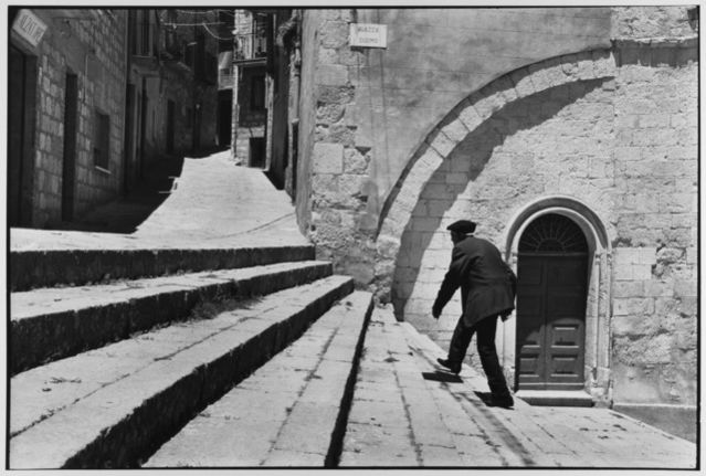 Man climbs stairs, Madonie Mountains, Petralina Sottana, Sicily, Italy, 1974 by Leonard Freed